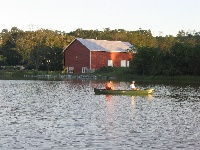 Fishing near red barn/rock bed